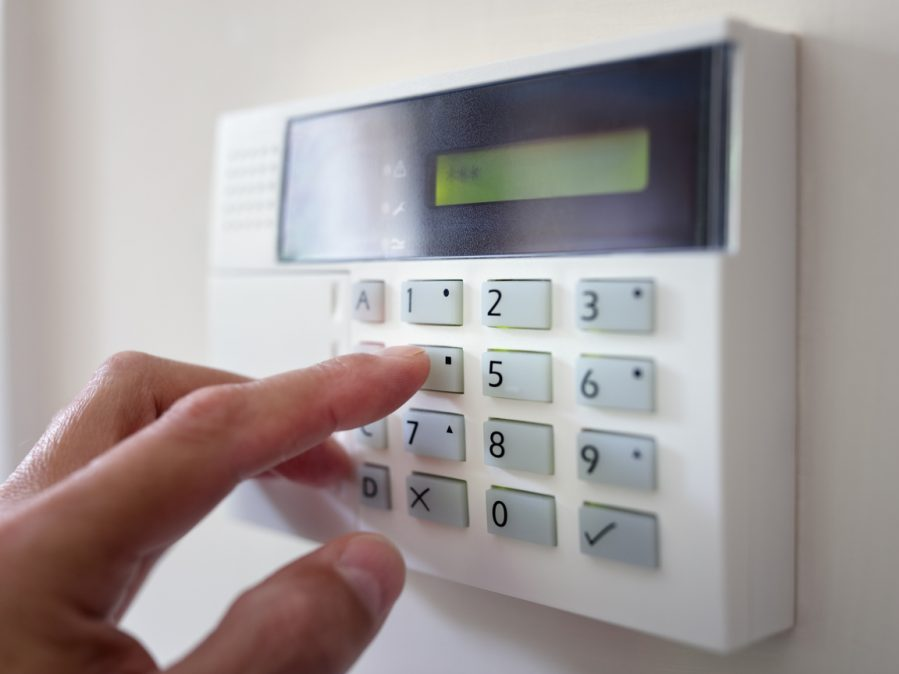 Security alarm keypad with person arming the system concept for crime prevention